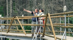 Hikers couple walking on the bridge in the woods and looking around HD - stock footage