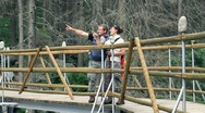 Stock Video Footage of Hikers couple walking on the bridge in the woods and looking around HD