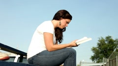 Girl reading book outdoors Stock Footage