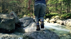Mun running, jumping on the rocks in the forest stream, slow motion HD Stock Footage
