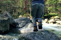 Mun running, jumping on the rocks in the forest stream, slow motion NTSC Stock Footage