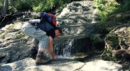 Stock Video Footage of Male hiker washing face, refreshing in the forest stream HD