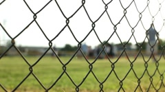 Football practice from behind fence dolly shot - stock footage