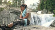 Stock Video Footage of Attractive woman talking on cellphone by the beautiful waterfall HD