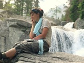 Stock Video Footage of Attractive woman talking on cellphone by the beautiful waterfall NTSC