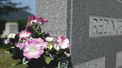 Flowers next to headstone in graveyard Stock Footage