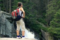 Stock Video Footage of Woman in the forest looking at beautiful waterfall NTSC