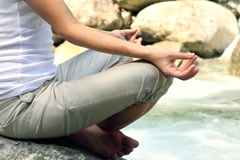 Woman meditating on the rocks by the stream NTSC Stock Footage