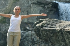 Woman meditating on the rocks, waterfall in the background NTSC Stock Footage