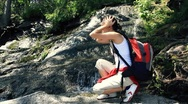 Stock Video Footage of Female hiker washing face, refreshing in the forest stream HD