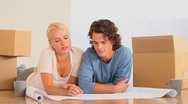 Couple planning how to set up their new livingroom Stock Footage