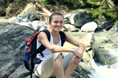 Portrait of young beautiful hiker sitting on a rock by the river Stock Footage