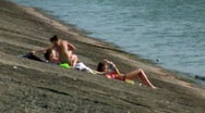 Stock Video Footage of Three girls sunbathing on the stones