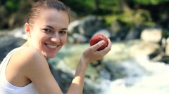 Young woman eats fresh apple, outdoors Stock Footage