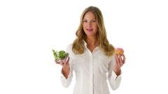 Woman deciding between salad and cupcake Stock Footage