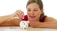 Woman putting money in piggy bank Stock Footage