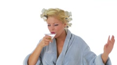 Woman with hair curlers and bathrobe drinking a martini Stock Footage