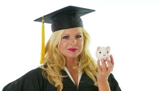 Young woman in graduation gown holding a piggy bank Stock Footage