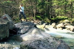 Mun running, jumping on the rocks in the forest stream, slow motion Stock Footage