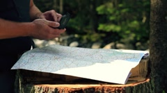 Man looking at map and compass in the woods Stock Footage