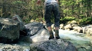 Womun running, jumping on the rocks in the forest stream, slow motion Stock Footage