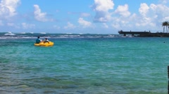 Puerto Rico - People on yellow paddle boat at a beatiful Caribbean beach Stock Footage