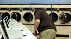 Man at Laundromat washing clothes Stock Footage