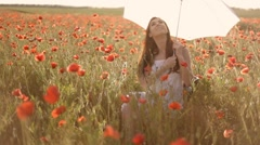 Young woman twisting white umbrella, sitting on chair among poppies Stock Footage