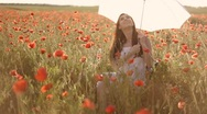 Stock Video Footage of Young woman twisting white umbrella, sitting on chair among poppies