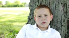 Boy against tree looking at camera Stock Footage