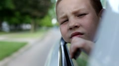 Boy hanging head from car window - stock footage
