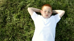 Young boy relaxing laying in grass Stock Footage
