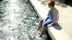 Lonely kid sitting by water Stock Footage