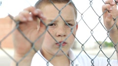 Boy with hands on fence looks at camera - stock footage