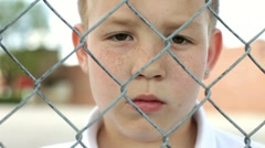 Close up of Upset Boy behind fence Stock Footage
