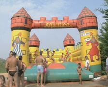 Children have fun on a bouncy castle / inflatable - stock footage