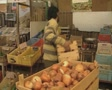 Crate of onions moved onto a market stall Footage
