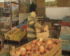 Crate of onions moved onto a market stall Stock Footage