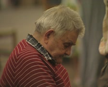 Grey haired man works sitting in the market Stock Footage