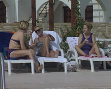 Three people relax on loungers Stock Footage