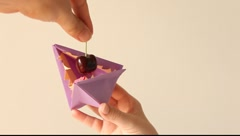 Origami monster eating cherry Stock Footage