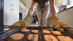 Woman Removes Baked Cookies From Oven Stock Footage