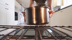 Woman Opens Oven And Puts Casserole Pot Inside Camera Inside Oven - stock footage