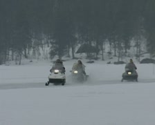 Snowmobiles head towards and then past the camera Stock Footage