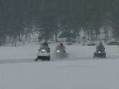 Stock Video Footage of Snowmobiles head towards and then past the camera