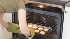 Woman Puts A Tray Of Cookies Into The Oven To Bake Stock Footage