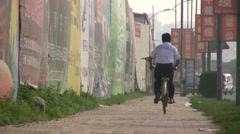 Man cycles past advertising billboards in China - stock footage