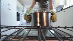 Woman Lifts Out Cooking Pot From The Oven Camera In The Oven Stock Footage