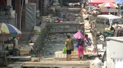 Two Chinese women are looking at waste and garbage at their local market - stock footage