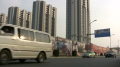 Traffic flows along new apartments in China Stock Footage